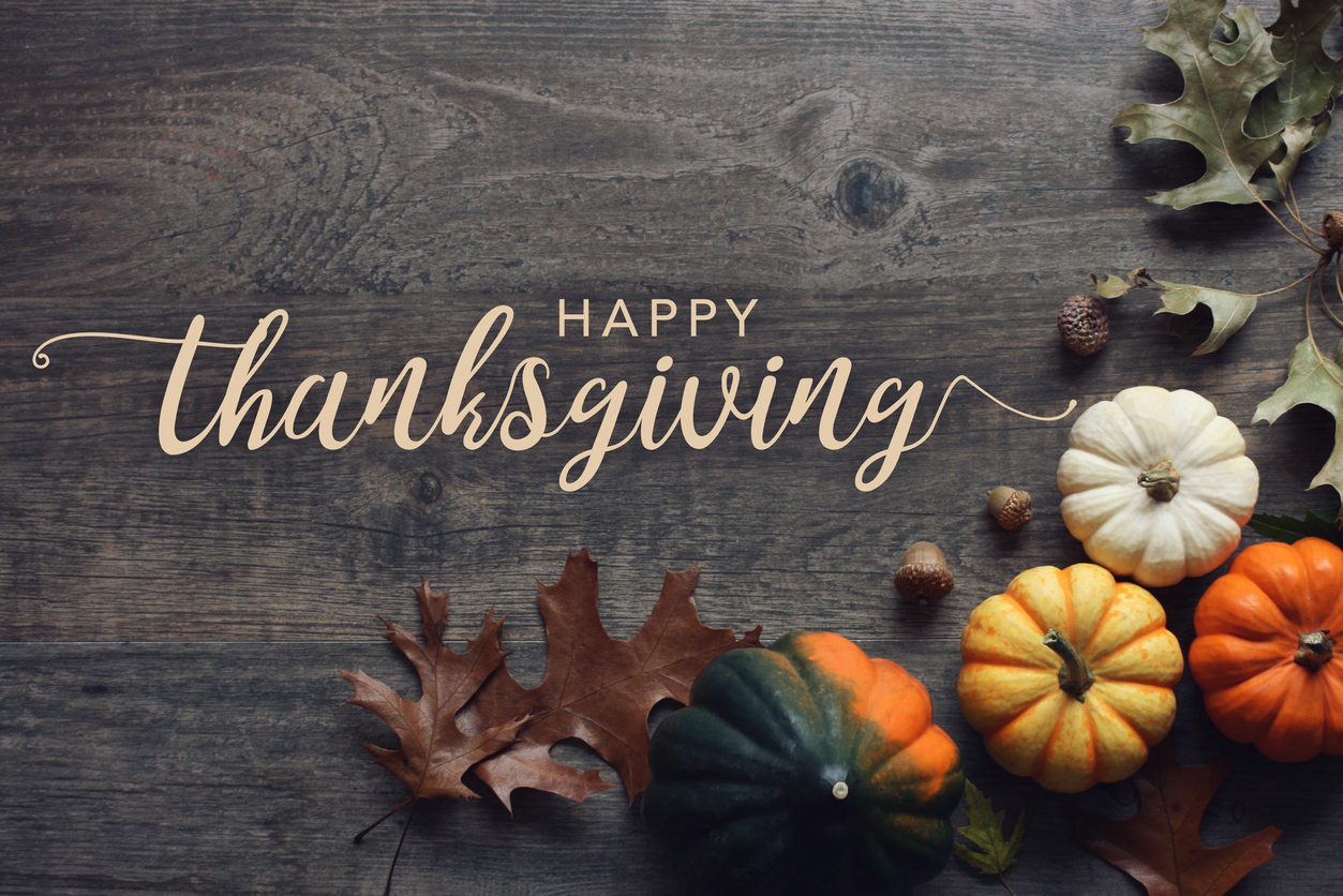 Happy Thanksgiving greeting text with fall pumpkins, squash and leaves over dark wood table background